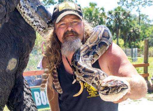 Photo of Dusty Crum carrying python.